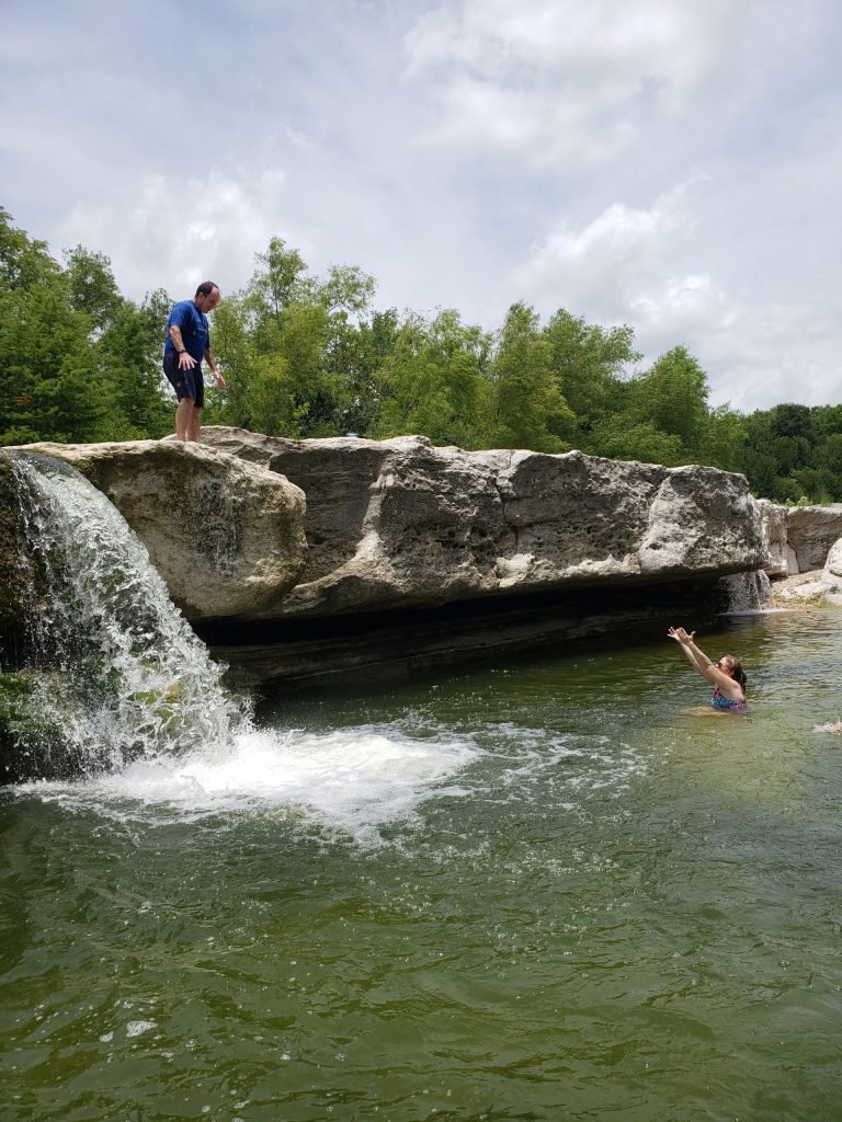 Man cliff jumping as woman catches him at mckinney falls state park
