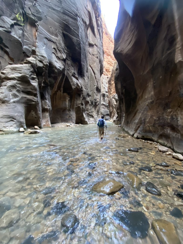 man hiking through the narrows in zion national park