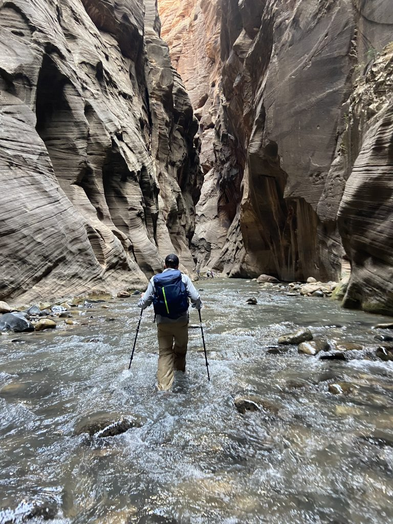 man walking through the narrows with hiking sticks