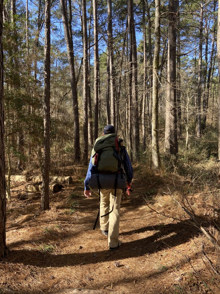 man with large backpack hiking the chinquapin trail