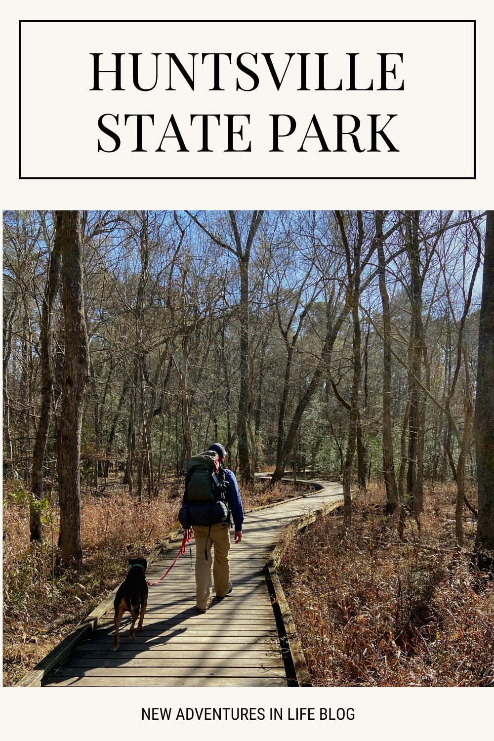 man with large backpack and dog walking along wooden walkway in huntsville state park