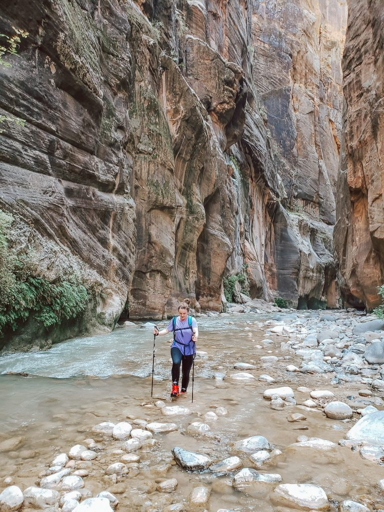 Girl in Purple hiking in river between two cliffs