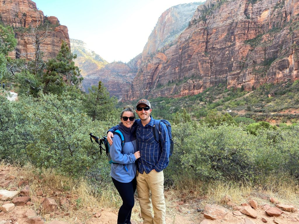 Couple both wearing blue and standing at the bottom of a canyon