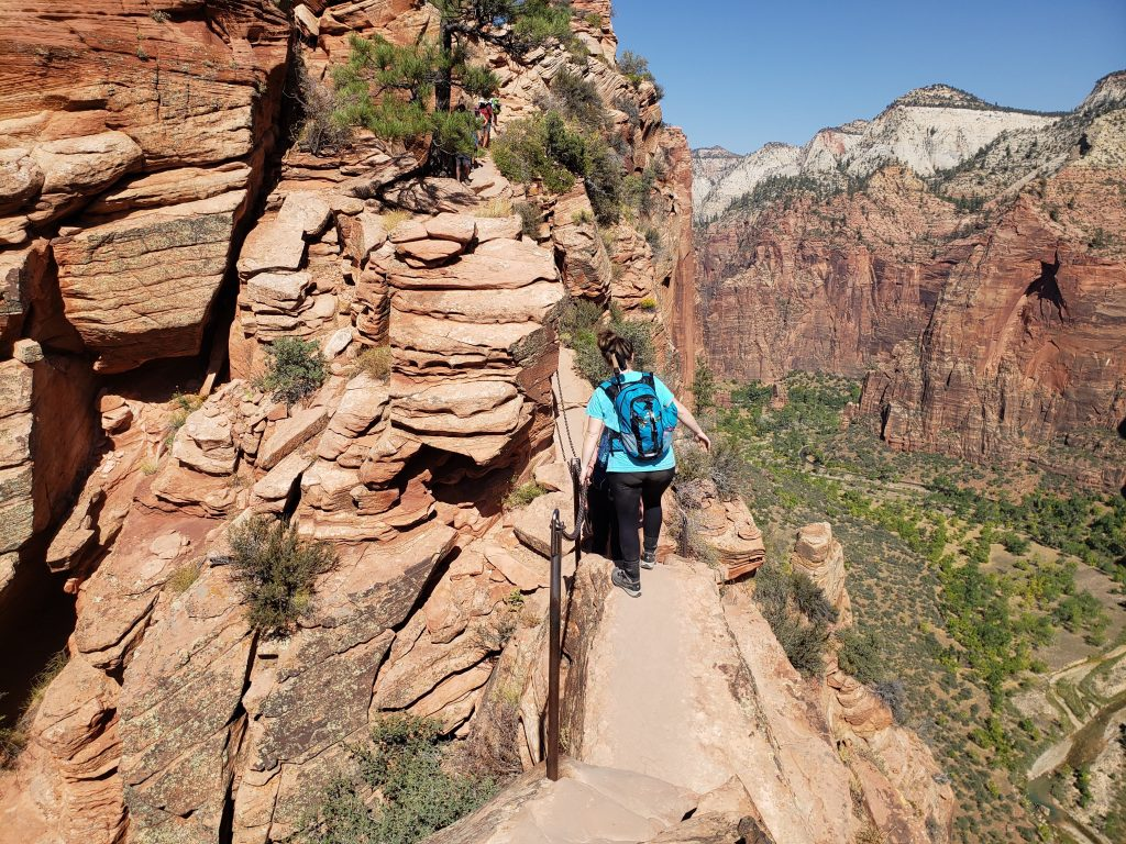 Girl hiking on a narrow edge and holding onto a chain for support