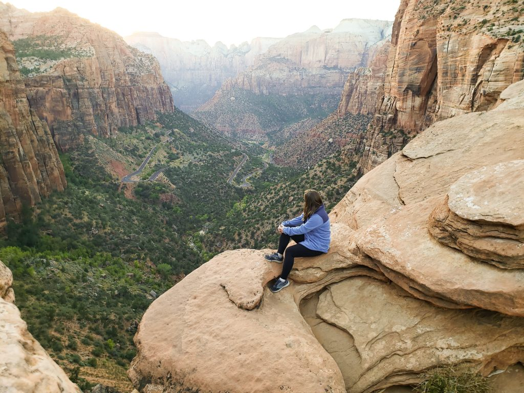 Girl wearing blue and sitting on the edge of a cliff overlooking a canyon