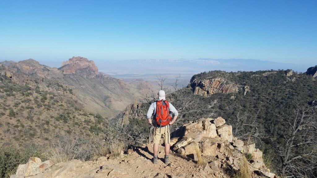 Man with orange backpack looking towards the mountains below him