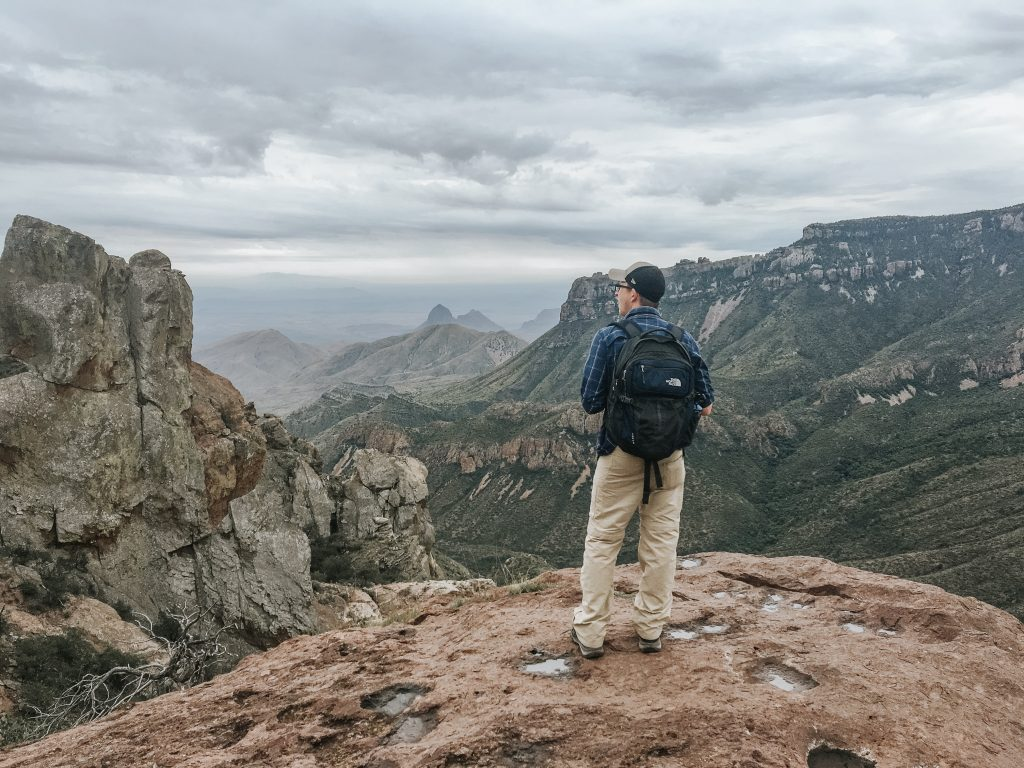 Man looking at view from top of mountain