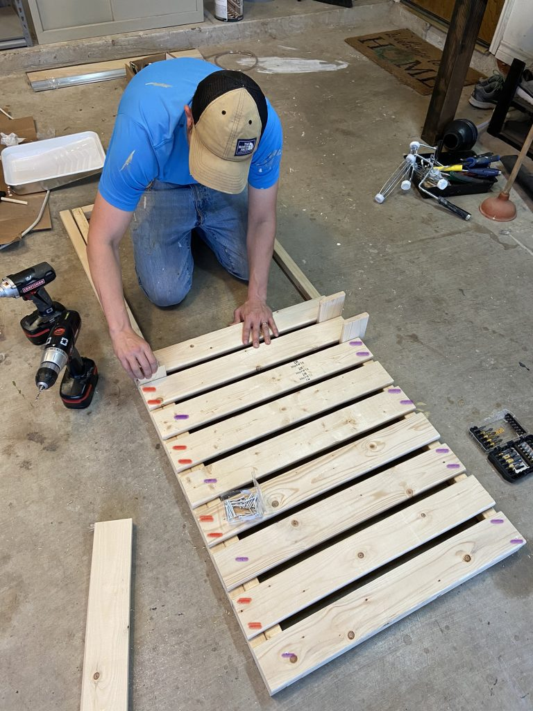 man building bed frame with wood spacers