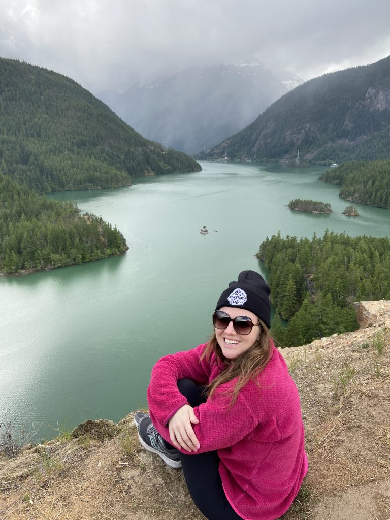 Girl sitting on cliff over lake