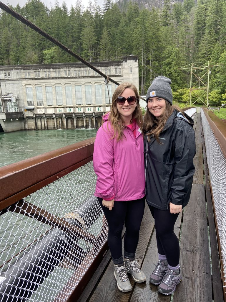 two girls standing on suspension bridge with powerhouse in the background