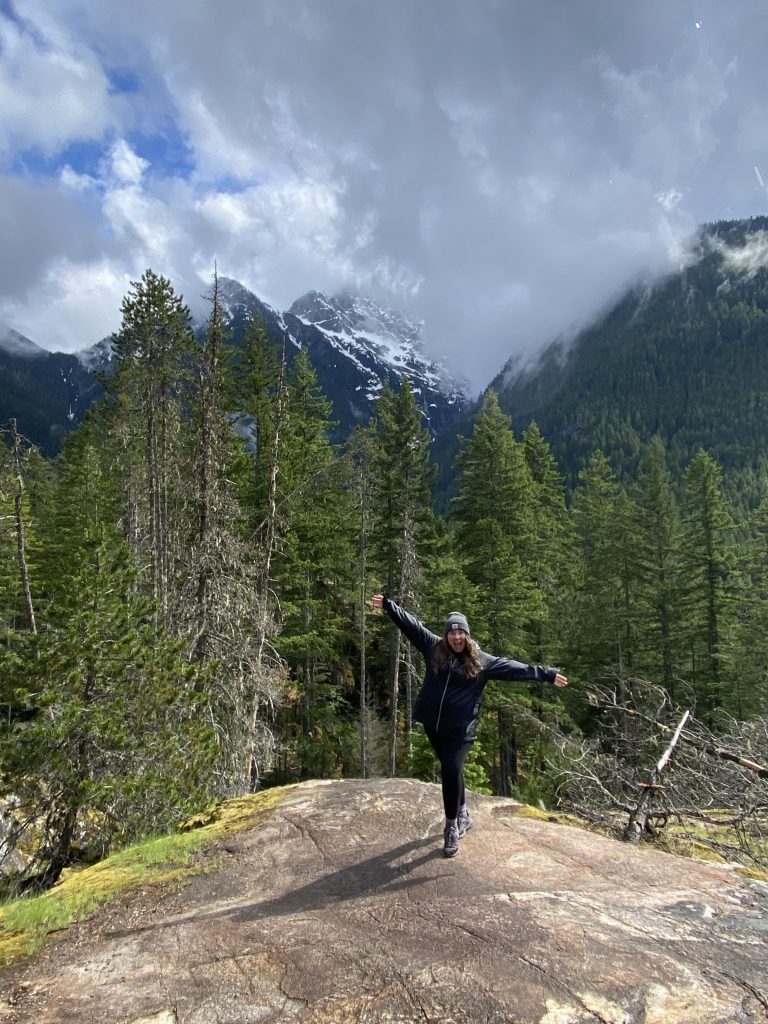 girl hiking with large trees and mountain in background