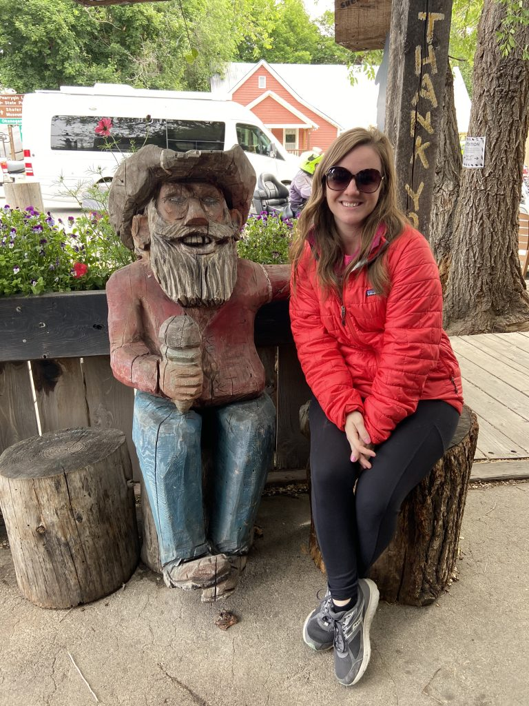 Girl sitting next to carved wooden statue